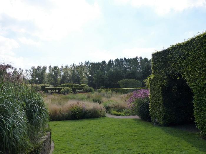Cette partie du jardin située à l'avant de l'ancien corps de ferme, la plus ancienne et la plus souvent photographiée, a été reprise par le paysagiste pour en faire une vaste prairie parcourue d'étroites allées en briques.
