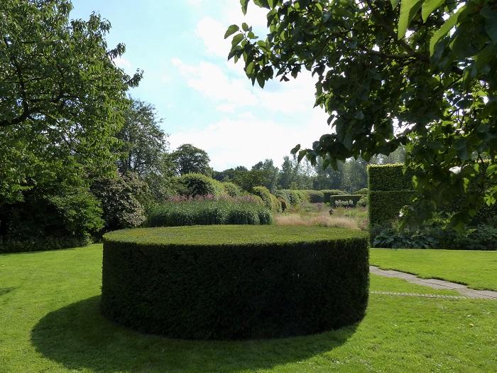 Posé sur la pelouse, ce rond d'ifs taillés apporte un effet structurant permanent. Grâce à sa géométrie douce, sans arêtes, il assure une forme de transition entre le partie du jardin proche de l'habitation, plus structurée, et le jardin de prairie qui s'étend jusqu'aux limites du terrain